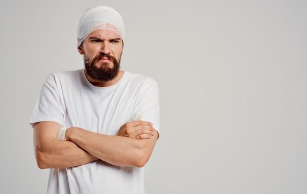 Mann im weißen t-shirt bandagierte kopfgesundheitsproblemverletzungsbehandlung