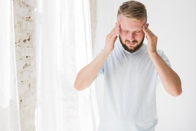 Mann im weißen t-shirt, das unter schmerz leidet