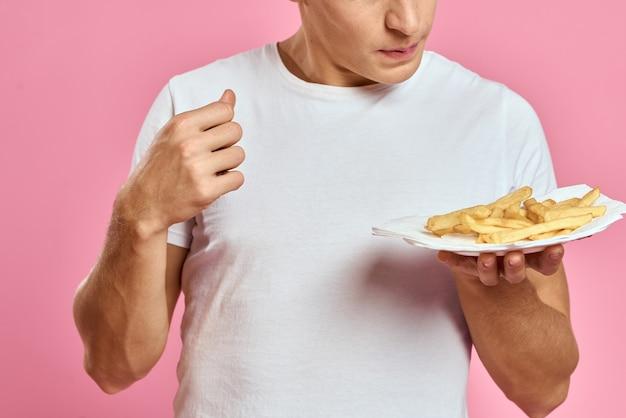 Mann im weißen t-shirt fast-food-kartoffeln diätfutter rosa hintergrund