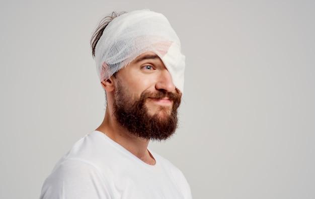 Mann im weißen t-shirt kopfverletzung gesundheitsbehandlung