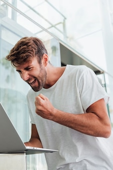Mann im weißen t-shirt mit laptop feiernd
