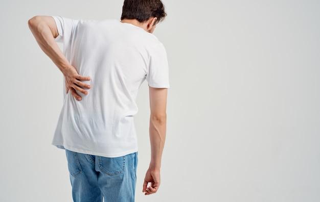 Mann im weißen t-shirt rückenschmerzen osteochondrose der wirbelsäule modell rückansicht