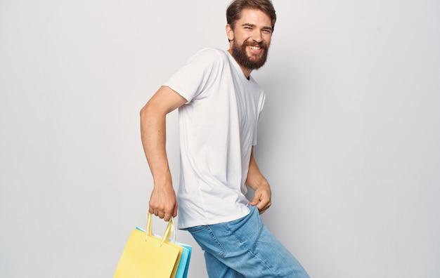 Mann im weißen t-shirt und in den jeans mit paketen in den händen, die spaß einkaufen, isolierte folie.