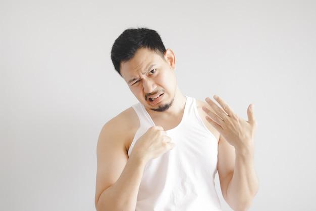 Mann im weißen trägershirt mit ausdruck des heißen wetters. konzept des heißen wetters der sonne in asien.