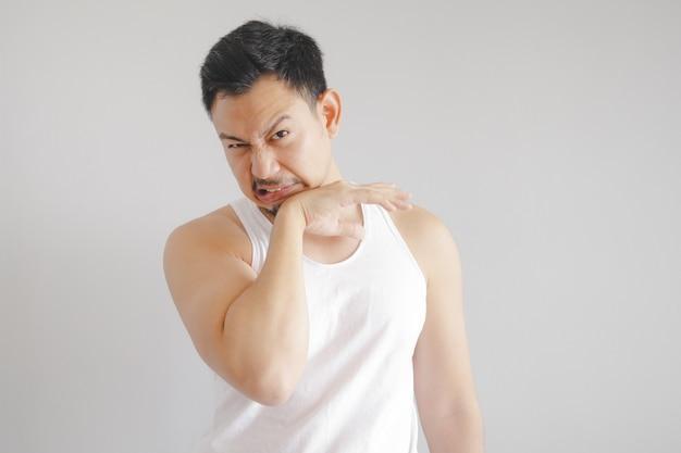 Mann im weißen trägershirt mit heißem wetterausdruck. konzept des heißen wetters der sonne in asien.