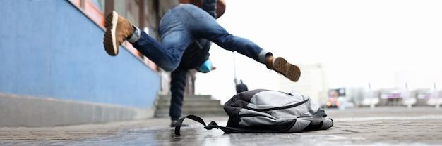 Mann im winterkleid slip auf bürgersteig mit eis nahaufnahme hintergrund