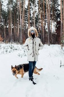 Mann im wintermantel im wald mit schäferhund