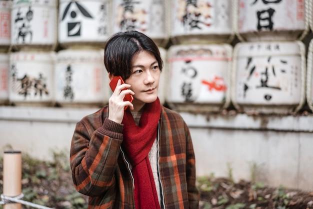 Mann im winteroutfit, das draußen am telefon spricht