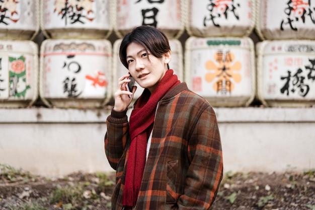 Mann im winteroutfit, der am telefon spricht