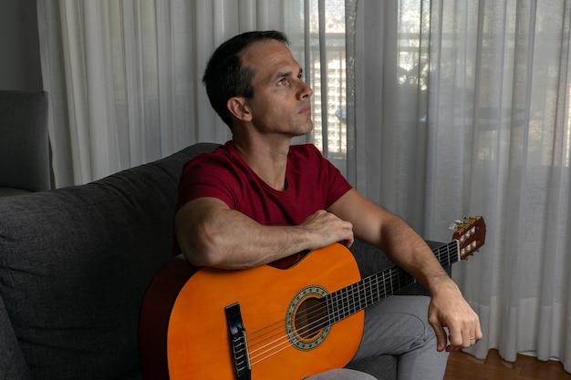 Mann im wohnzimmer mit gitarre und nach oben schauend.