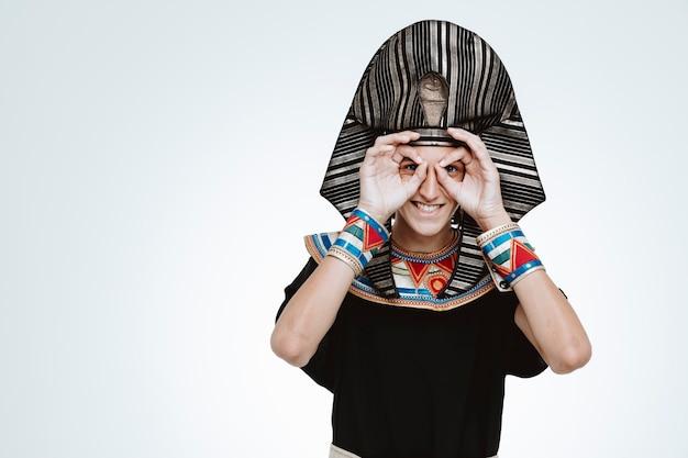 Mann in altägyptischem kostüm, der eine binokulare geste durch die finger macht, die fröhlich auf weiß lächelt