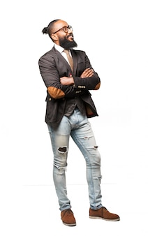 Mann in anzug und jeans mit gekreuzten armen