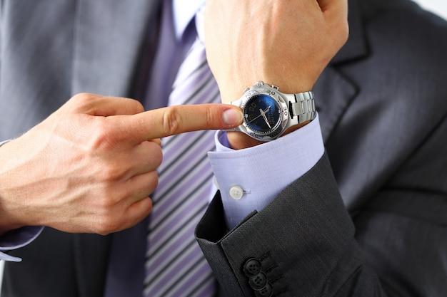 Mann in anzug und krawatte checken zeit bei silberner armbanduhr aus