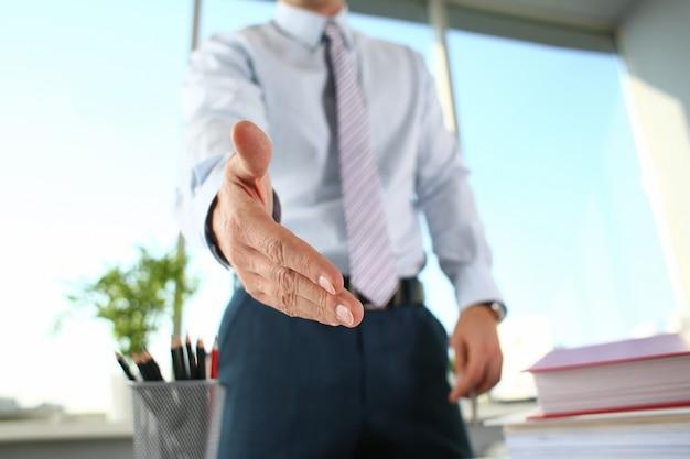 Mann in anzug und krawatte geben hand als hallo