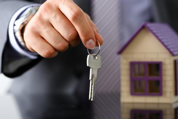 Mann in anzug und krawatte halten in der hand silber schlüssel geben