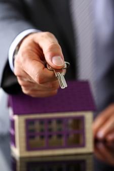 Mann in anzug und krawatte halten in der hand silbernen schlüssel