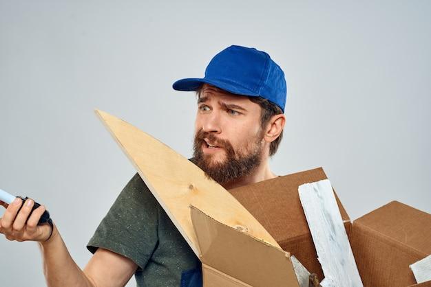 Mann in arbeitskleidung mit box in händen