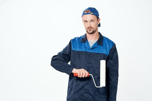 Mann in arbeitsuniform wandmalerei reparaturservice. foto in hoher qualität