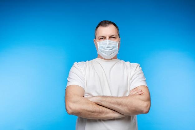 Mann in aseptischer maske mit verschränkten armen