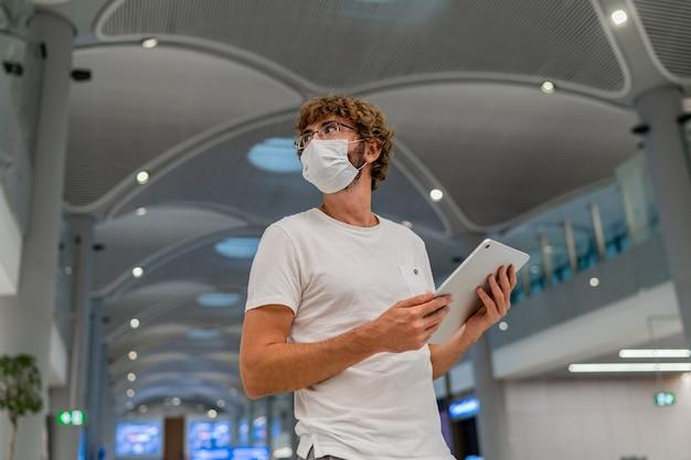 Mann in atemschutzmaske wartet nächstes flugzeug am flughafen und benutzt tablette.