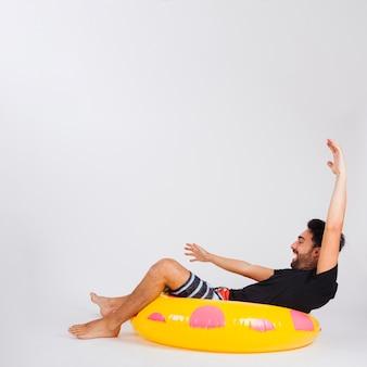 Mann in beachwear, die spaß im schwimmenden schlauch hat