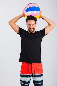 Mann in beachwear halten ball hinter kopf