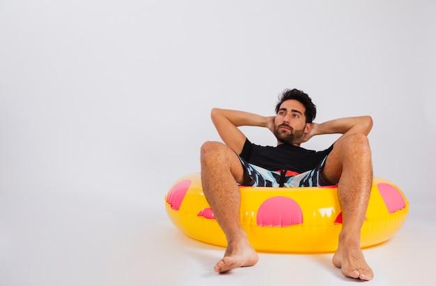 Mann in beachwear liegen in schwimmenden rohr