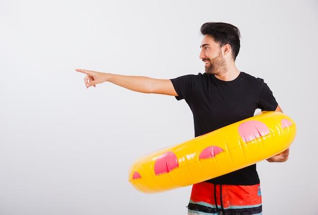 Mann in beachwear mit schwimmenden rohr zeigt auf die seite close up view