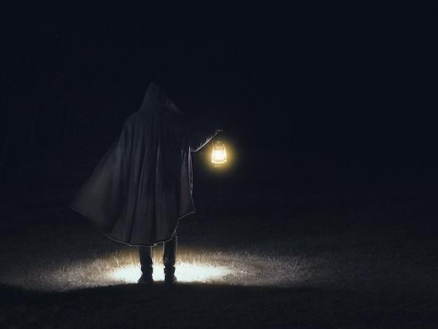 Mann in bewegung in schwarzen kleidern, die die leuchtende laterne auf der dunklen szene halten.