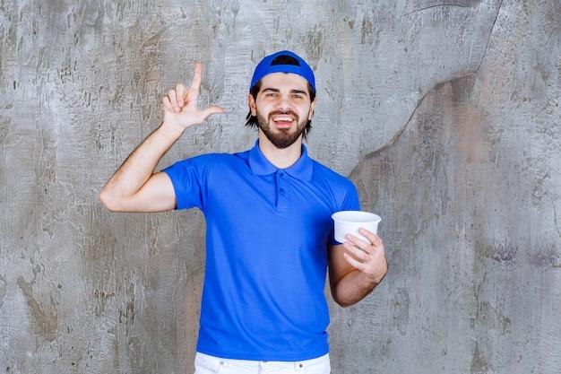 Mann in blauer uniform, der einen plastikbecher zum mitnehmen hält und nachdenklich aussieht
