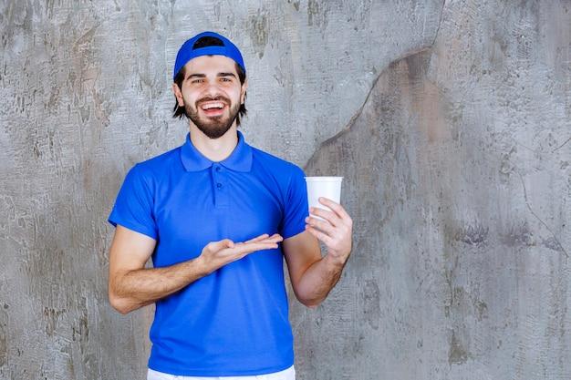 Mann in blauer uniform mit einem getränk zum mitnehmen