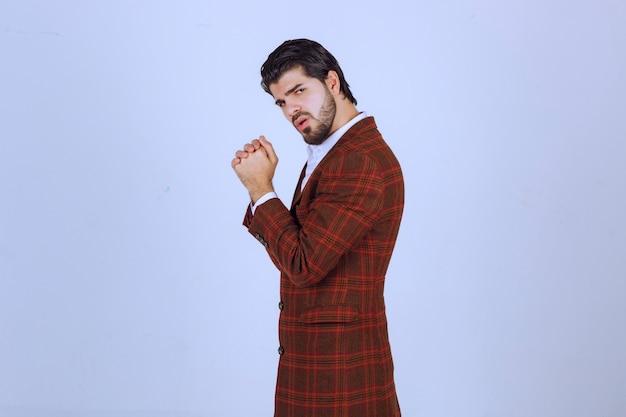 Mann in braunem blazer, der seine handflächen vereinigt und um etwas bittet.