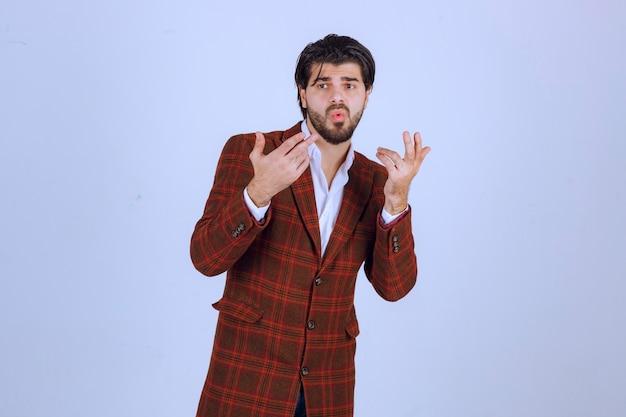 Mann in braunem blazer sieht verwirrt aus und versucht sich zu erklären.