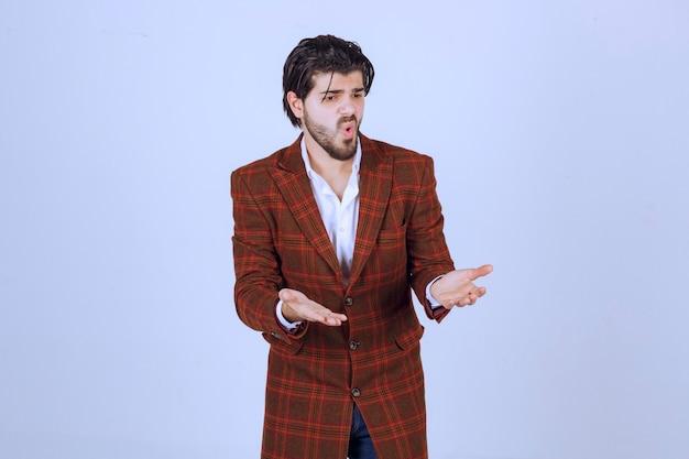 Mann in brauner jacke machte einen fehler und versuchte sich mit offenen händen zu erklären.