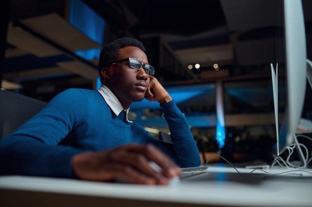 Mann in brille arbeitet am computer, büro lebensstil. männliche person am schreibtisch, dunkles interieur, moderner arbeitsplatz