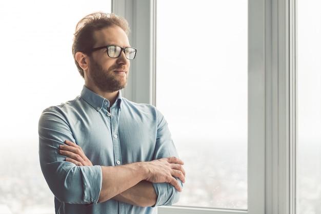 Mann in brille schaut aus dem fenster
