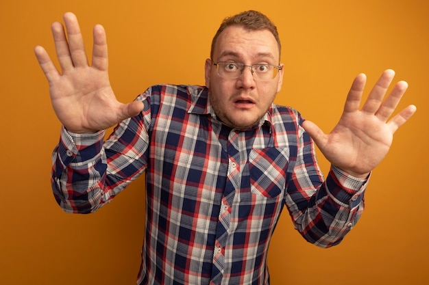 Mann in brille und kariertem hemd besorgt mit erhobenen händen in der übergabe stehend über orange wand