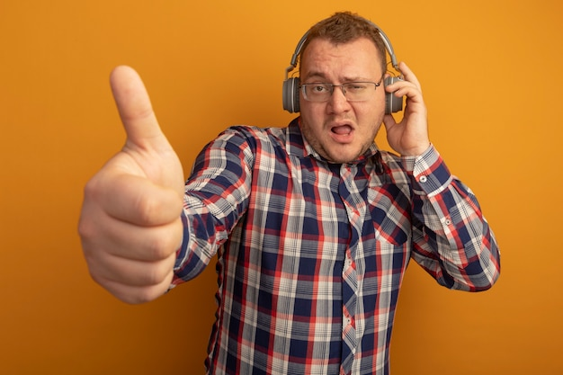 Mann in brille und kariertem hemd mit kopfhörern zeigt daumen hoch mit selbstbewusstem ausdruck, der über orange wand steht