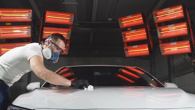 Mann in brille und maske, ein beatmungsgerät poliert das auto mit einem schwamm und einer speziellen chemischen zusammensetzung, um den lack auf der karosserie vor kratzern zu schützen