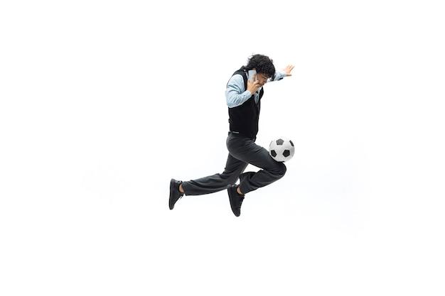 Mann in bürokleidung, der fußball oder fußball mit ball auf weißem hintergrund spielt ungewöhnliches aussehen für