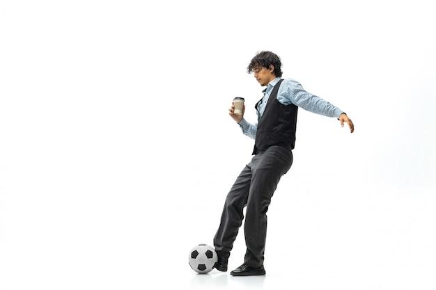 Mann in bürokleidung, die fußball oder fußball mit ball auf weißem raum spielt. ungewöhnlicher blick für geschäftsmann in bewegung, aktion. sport, gesunder lebensstil.