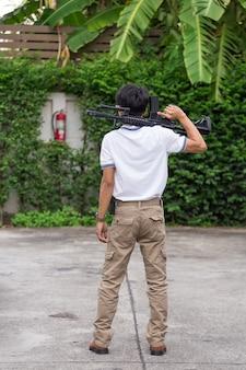 Mann in cargo-hosen mit waffe