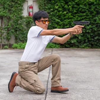 Mann in cargohosen mit pistole