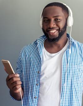 Mann in den kopfhörern hört musik unter verwendung des intelligenten telefons