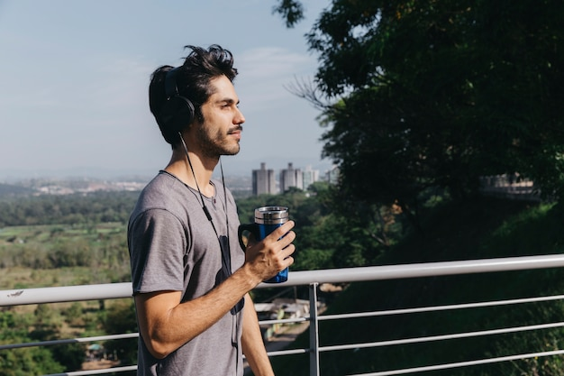 Mann in den kopfhörern mit thermocup am handlauf