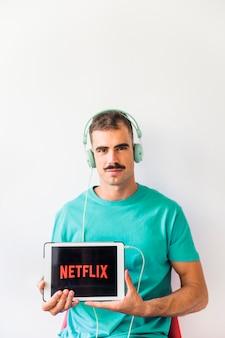 Mann in den Kopfhörern, die Netflix-Logo zeigen