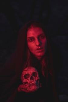 Mann in den schatten des roten lichtes, die in der dunkelheit mit dem schädel sitzen
