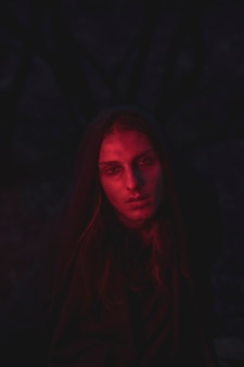 Mann in den schatten des roten lichtes, die in der dunkelheit sitzen