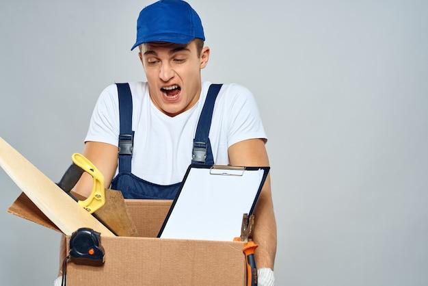 Mann in der arbeitsuniform mit einer box in seinen händen werkzeuglader lieferung licht hintergrund. hochwertiges foto