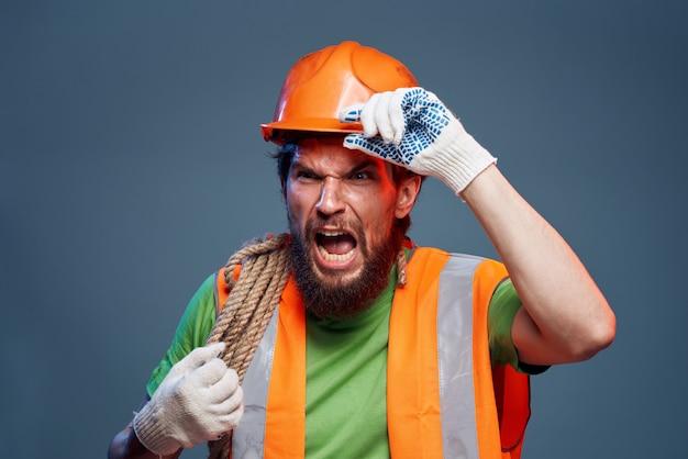Mann in der arbeitsuniform orange farbseil in den händen
